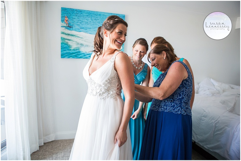 Bride's mother and sisters zip her into her gorgeous beachy wedding gown.