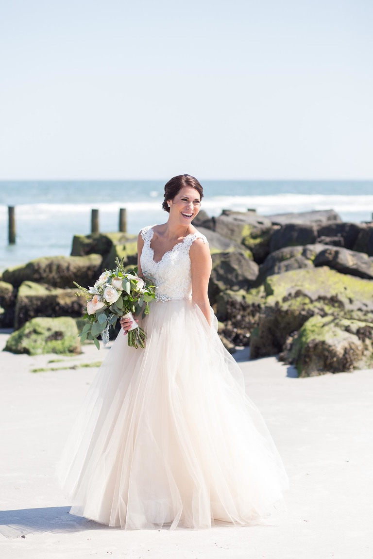 A bride laughs on the beach at her The Reeds at Shelter Haven wedding.