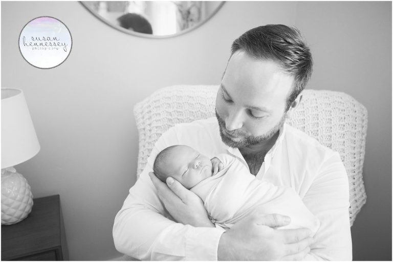 Black and white portrait of father and newborn in her nursery