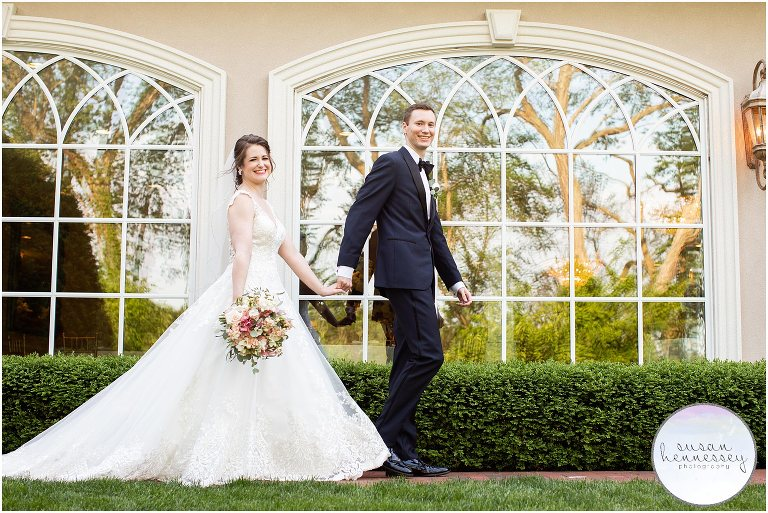Bride and groom walk along unique windows at South Jersey wedding venue