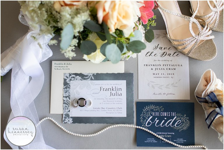 Bridal details featuring invitation, wedding bands, pearl necklace, garter and shoes.