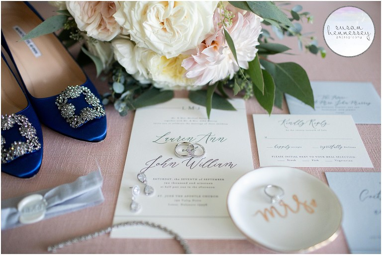Bridal details featuring the bride's bouquet, invitation, wedding bands and blue manolo blahnik shoes.