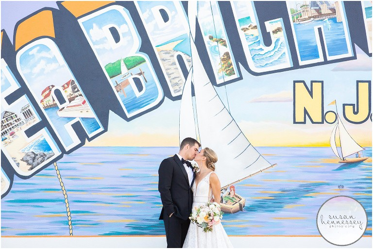 A bride and groom pose at the Welcome to Sea Bright mural on their wedding day
