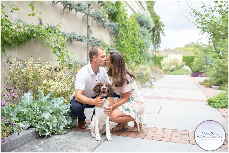 An engaged couple kiss while photographed with their dog.