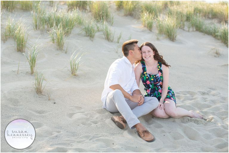 Happily engaged couple sit on the beach at their Bradley Beach Engagement Session