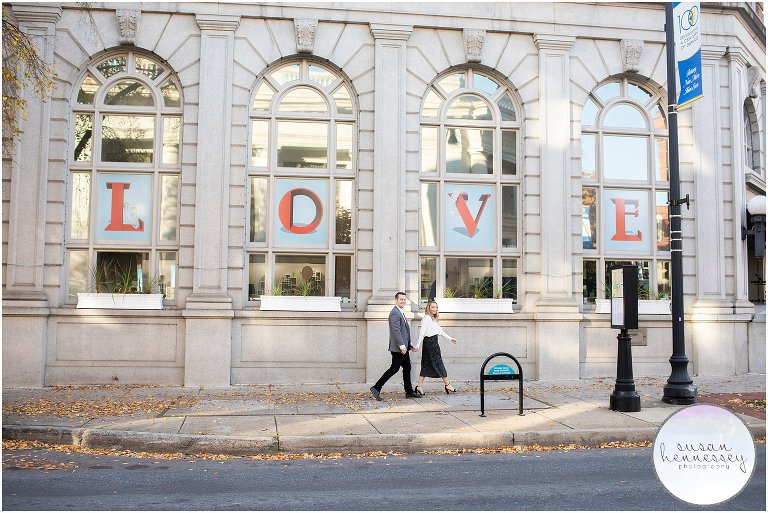 A couple hold hands while walking at their Downtown Frederick Engagement Session