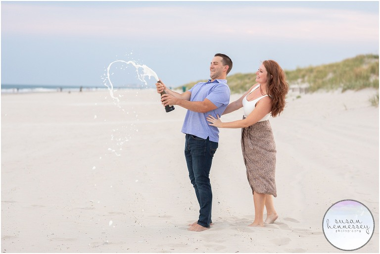A couple pops champagne on the breach after their surprise proposal in Stone Harbor