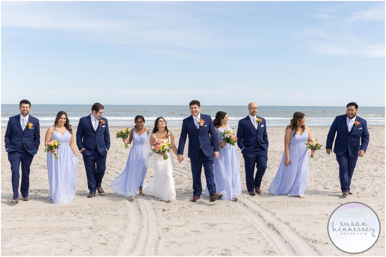 Bridal party walk on beach with ocean in the background at ICONA Avalon Wedding